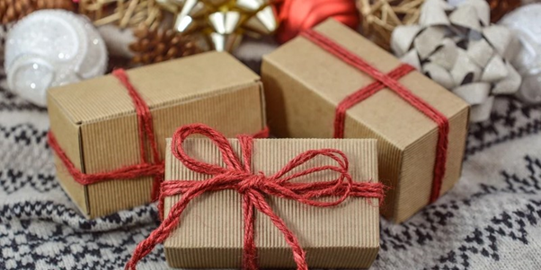 Recyclable cardboard gift packaging wrapped in red ribbon